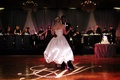 Bride in a strapless Amsale gown dances with groom in black tuxedo