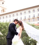 groom and bride with long veil in front of Breakers Resort