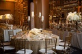 Wedding reception table with textured linens, gold chairs, gold-rimmed glassware, tall candle