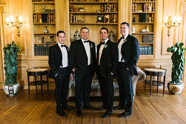 Wedding party groomsmen tuxedo suits bow ties in library at Oheka Castle