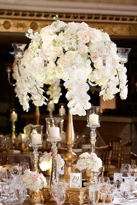 Orchid, hydrangea, ranunculus wedding flower arrangement on gold stand mercury glass candle holders