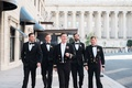 Groom in navy uniform with white bow tie with groomsmen in tuxedos and bow ties with one in uniform