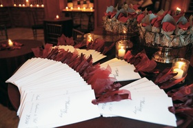 Display of white and red wedding programs and wedding petal toss cones