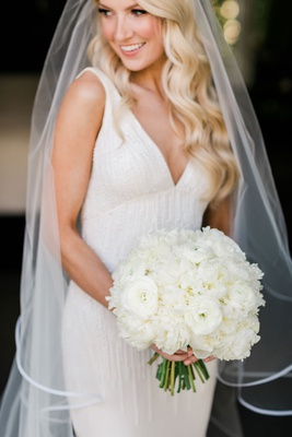 bride with long blonde hair holding white bouquet ranunculus peony flowers green stems