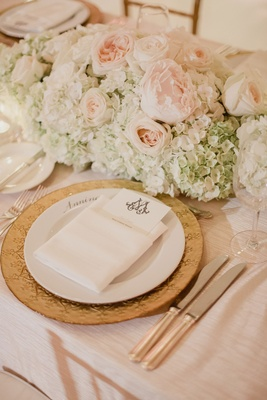 Wedding reception table gold charger plate menu in napkin with monogram and hydrangea peony roses