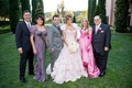Bride in Mark Zunino ruffle wedding dress with mother of bride in bright pink gloves and groom