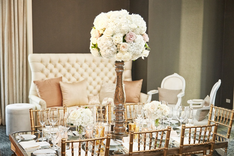 tall rose centerpiece with high base on table with gold chiavari chairs