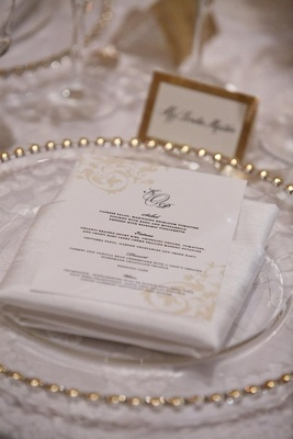 White menu card on gold-rimmed charger plate