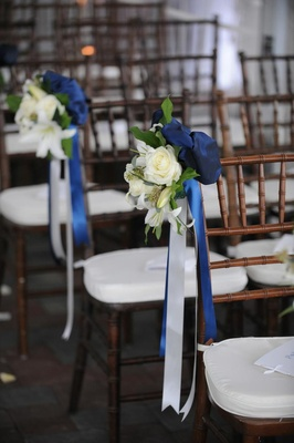 White rose and lily with blue and white ribbon along aisle