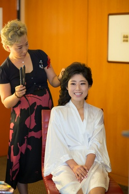 Korean American bride getting hair done in white silk robe