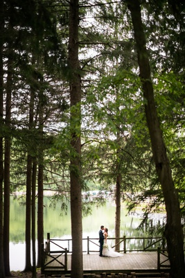 wedding location new york summer camp feel bride groom portrait on dock deck tall trees forest