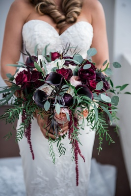 Bride in sweetheart neckline wedding dress holding dark burgundy bouquet greenery freshly picked