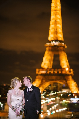 Bride in satin Melany Rowe dress with pearls and groom in tuxedo by the Eiffel Tower in Paris