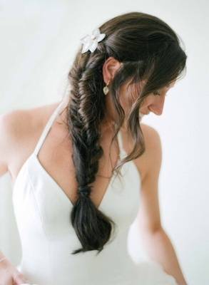 Bride with white V-neck vera wang halter gown with brown hair fishtail braid flower hair accessory
