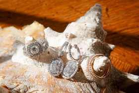 double halo engagement ring with halo earrings and rose gold wedding rings on conch shell