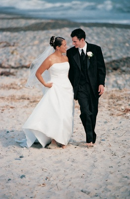 Bride and groom walk on the beach in their wedding dress and tuxedo
