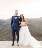 Bride in Monique Lhuillier wedding dress horsehair hem strapless holding groom's arm navy blue suit