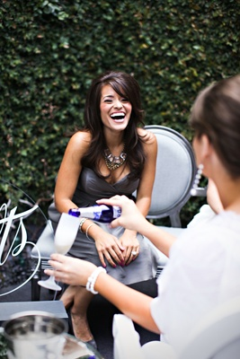 Bride-to-be laughs and guest pours champagne