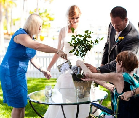 Bride and groom with mothers watering small tree