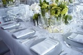 Silver charger plates with white and green flower centerpieces