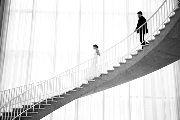Black and white photo of bride and groom walking down winding staircase at Chicago History Museum
