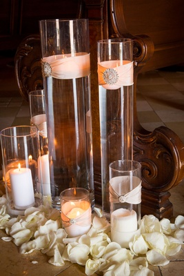 Candles in hurricane vases wrapped in blush ribbon with jewel