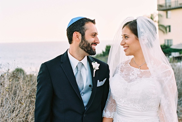 Groom in dark suit with blue tie vest and yarmulke with bride in lace Alfred Angelo wedding dress