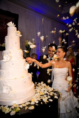 Bride and groom cut white wedding cake