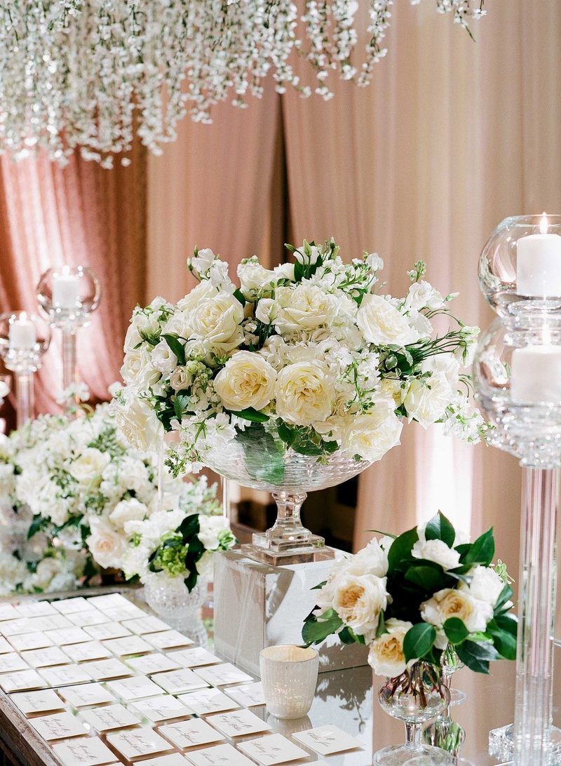 Escort cards on mirror table with clear vases filled with garden roses and other white flowers