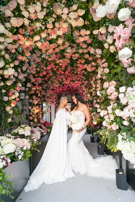 Brides same sex wedding gay ceremony under tunnel of roses and greenery at rooftop venue