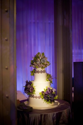 White wedding cake with purple flowers made of sugar