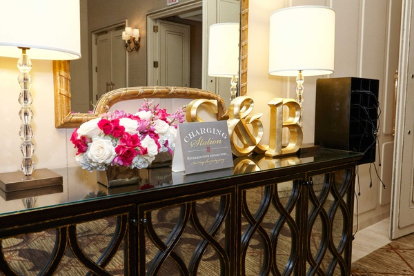 Phone charging station with monogram letter initials and pink white flowers ballroom reception