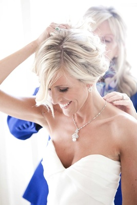 Mother of bride puts necklace on blonde bride