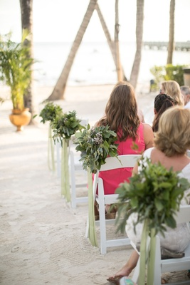Wedding guests sitting on white foldable chairs beach ceremony greenery on ends of chairs