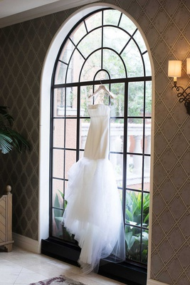 vera wang strapless wedding dress hanging in black frame arch window of venue tulle skirt
