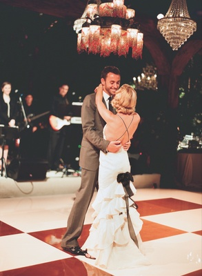 Bride in a Carolina Herrera gown dances with a groom in a grey Tom Ford suit