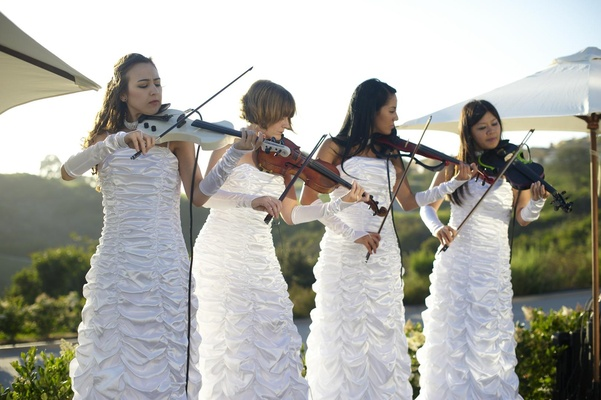 Four women in white dresses and gloves with string intruments