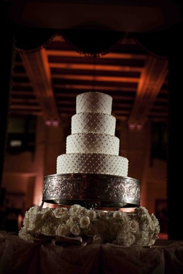 Four layer round cake with swiss dots on silver stand