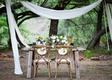 Rustic wood sweetheart table and chairs with Mr. and Mrs. wood signs