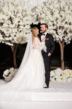 bride in long sleeve marchesa wedding dress groom in tuxedo white cherry blossom trees white stage