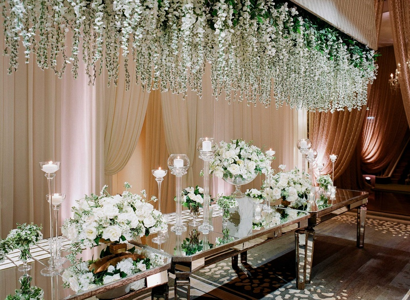 Mirror table with white flower and greenery installation over table, white rose escort card table