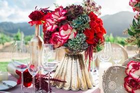 red and white flower floral arrangement in gold vase pink table linen vineyard
