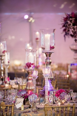 candlesticks and hurricanes with fuchsia flowers on wedding reception table
