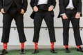 groomsmen in tuxedo showing red socks