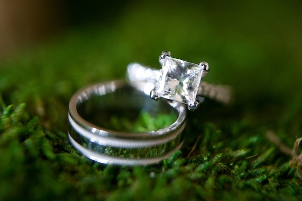Diamond wedding ring and men's band on grass