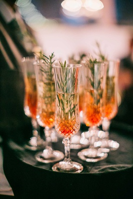 holiday wedding toast champagne flutes with champagne red berry and rosemary sprig