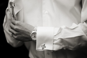 Black and white photo of groom wearing fleur de lis cufflink and watch