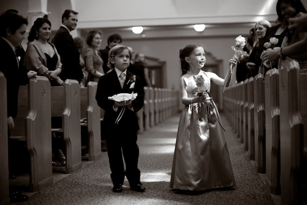 Black and white photo of flower girl handing flowers to guests