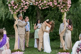 Bride and groom kiss at garden wedding altar
