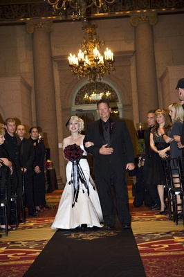 Bride in a strapless Alvina Valenta gown and black sash walks down the aisle with father